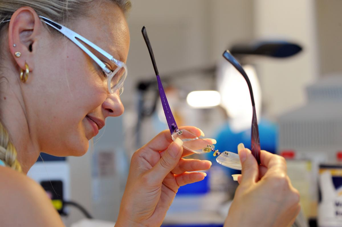 Optician Linda Bajerski mounts lenses into rimless glasses at Essilor Lenses in Rathenow, Germany