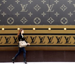 A woman carrying an iconic Hérmes Birkin bag walks past a huge Louis Vuitton suitcase ad in Shanghai