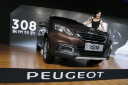 A model poses beside the Peugeot 2008 at the Guangzhou 2013 Auto Show