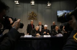 Andrew Forrest (centre back) watches over as religious leaders sign his agreement to slavery in their supply chains